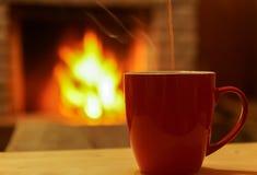 Taza de té en fondo del bokeh de la chimenea Fotos de archivo libres de regalías