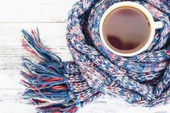 Taza de té en la tabla de madera envuelta en la opinión superior tejida caliente de la bufanda Imagen de archivo