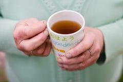 Taza de té en las manos de una más vieja mujer Fotografía de archivo libre de regalías