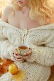 Taza de té en las manos de una muchacha en un suéter blanco Fotografía de archivo libre de regalías