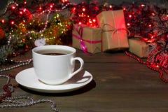 Taza de té en los juguetes de una Navidad del fondo, regalos Fotografía de archivo