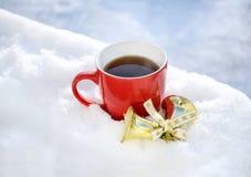 Taza de té en nieve en la decoración del humor y de la Navidad del invierno de la mañana Imagen de archivo