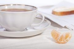 Taza de té en un platillo con un emparedado y un tangerin Foto de archivo