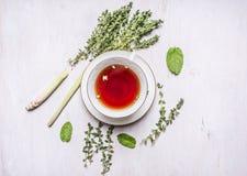 Taza de té en un platillo con un sistema de tomillo de la infusión de hierbas, menta, hierba de limón en cierre rústico de madera Fotos de archivo libres de regalías