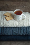 Taza de té en un suéter de la pila Foto de archivo