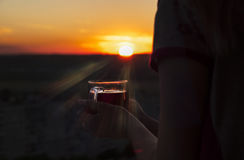 Taza de té en una puesta del sol Fotos de archivo libres de regalías