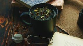 Taza de té entre los libros almacen de metraje de vídeo
