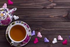 Taza de té de la tetera con los corazones en la tabla de madera marrón Imagen de archivo