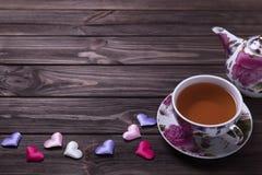 Taza de té de la tetera con los corazones en la tabla de madera marrón Fotos de archivo