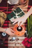 Taza de té, libro, flores Manos Visión superior Imagen entonada fotografía de archivo libre de regalías