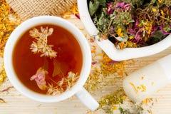 Taza de té, mortero, maja con las hierbas curativas Fotos de archivo libres de regalías