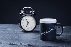 Taza de té negro con el despertador en una tabla Imágenes de archivo libres de regalías