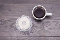 Taza de té negro con el merengue delicioso sabroso en la tabla de madera marrón Foto de archivo libre de regalías
