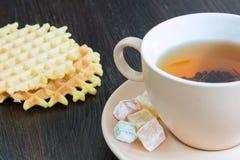 Taza de té negro con la oblea en el fondo oscuro Imágenes de archivo libres de regalías