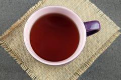 Taza de té negro en harpillera Fotografía de archivo