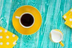 Taza de té negro en la placa amarilla Fotos de archivo libres de regalías
