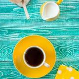 Taza de té negro en la placa amarilla y el jarro de leche amarillo Foto de archivo libre de regalías
