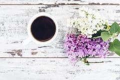 Taza de té negro en la tabla de madera del vintage con la rama de la lila Imagenes de archivo