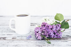 Taza de té negro en la tabla de madera del vintage con la rama de la lila Fotografía de archivo