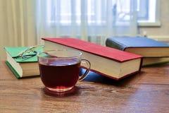 Taza de té negro y algunos libros en la tabla Imagenes de archivo