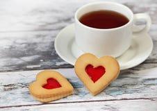 Taza de té negro y de galletas en forma de corazón Fotos de archivo