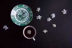 Taza de té negro y un platillo con una imagen de un dragón adornado con las pequeñas flores blancas Imagen de archivo