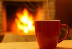 Taza de té o de café en fondo del bokeh de la chimenea Fotos de archivo libres de regalías