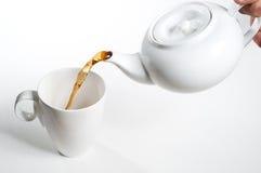 Taza de té que es vertido Fotos de archivo libres de regalías