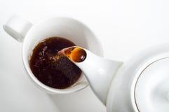 Taza de té que es vertido Imagenes de archivo