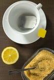 Taza de té, rebanadas de limón y azúcar marrón Imagen de archivo