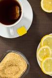 Taza de té, rebanadas de limón y azúcar marrón Foto de archivo libre de regalías