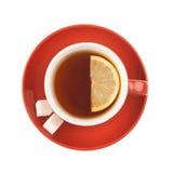 Taza de té roja con el azúcar y el limón. Fotografía de archivo