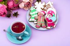 Taza de té rojo con el pan de jengibre de la Navidad del pan de jengibre Imágenes de archivo libres de regalías