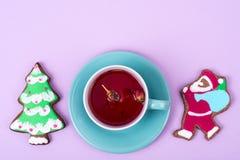 Taza de té rojo con el pan de jengibre de la Navidad del pan de jengibre Fotografía de archivo