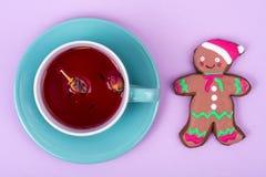 Taza de té rojo con el pan de jengibre de la Navidad del pan de jengibre Fotos de archivo
