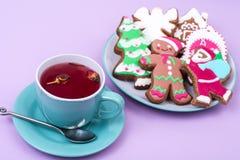 Taza de té rojo con el pan de jengibre de la Navidad del pan de jengibre Foto de archivo libre de regalías