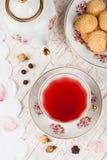 Taza de té rojo en la tabla de la porción Imágenes de archivo libres de regalías