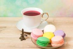 Taza de té rojo y de tortas coloreadas Imagen de archivo