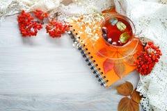 Taza de té, de serbal y de libreta en la tabla de madera Aún-vida del otoño Imagenes de archivo