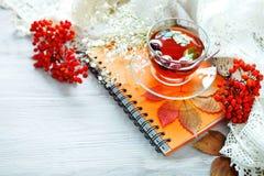 Taza de té, de serbal y de libreta en la tabla de madera Aún-vida del otoño Fotos de archivo libres de regalías