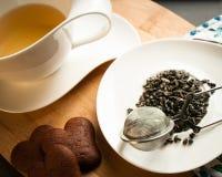 Taza de té servida con las galletas del chocolate Foto de archivo