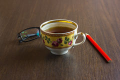 Taza de té, teléfono móvil, lápiz, vidrios en la mesa de madera de la oficina Foto de archivo