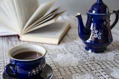 Taza de té, tetera y libro Imagen de archivo