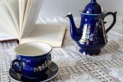 Taza de té, tetera y libro Fotos de archivo libres de regalías