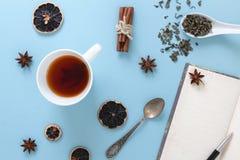 Taza de té verde preparado, con el cuaderno y la pluma en blanco abiertos, en fondo azul con los objetos relevantes imágenes de archivo libres de regalías