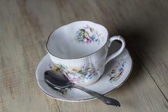 Taza de té y cuchara antiguas en el fondo de madera Imagenes de archivo