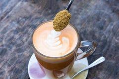 Taza de té y cucharilla que vierten el azúcar natural Fotografía de archivo