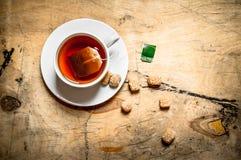 Taza de té y de azúcar de caña Fotos de archivo