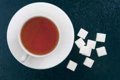 Taza de té y de azúcar de terrón en un fondo azul Fotos de archivo