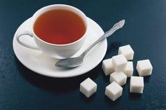 Taza de té y de azúcar de terrón en un fondo azul Fotografía de archivo libre de regalías